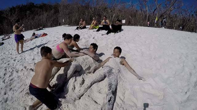 a family covering the kids in sand at the beach