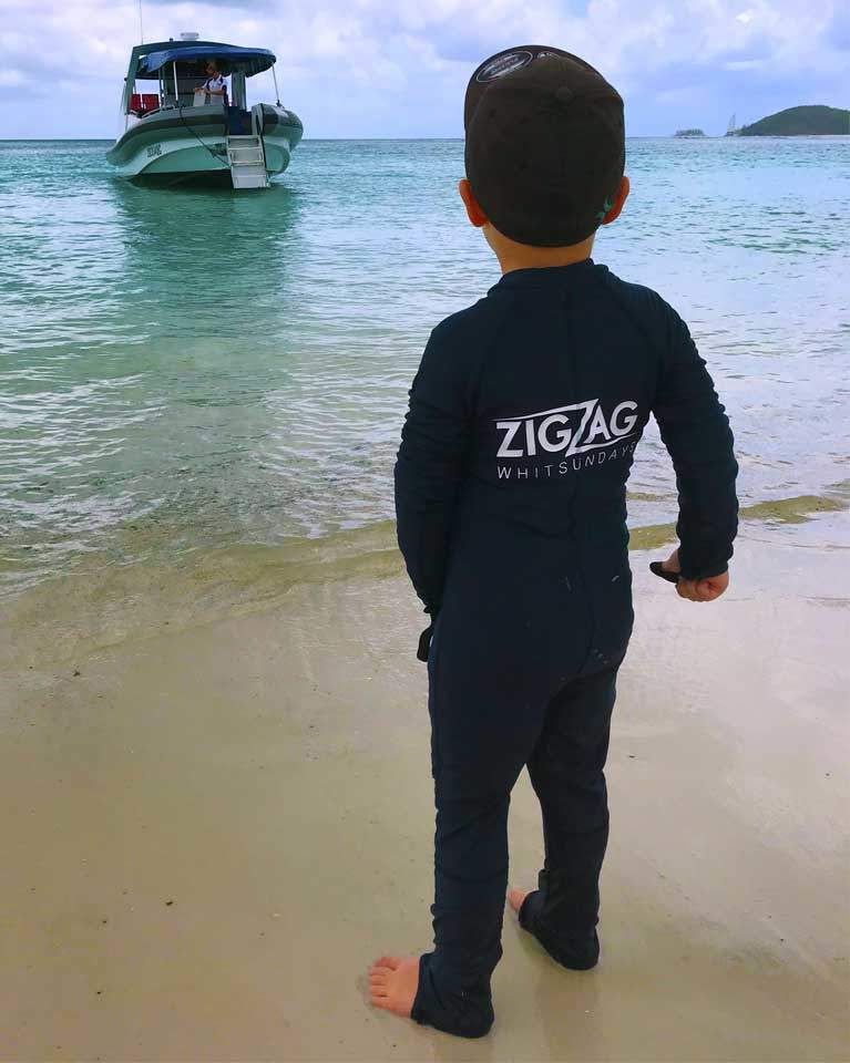 child standing on Whitehaven Beach in a zigzag wet suit